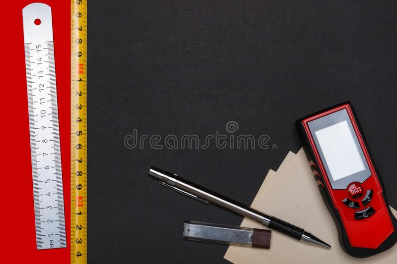 Measuring tools and automatic pencil with paper for notes on black and red background. View from above stock photos