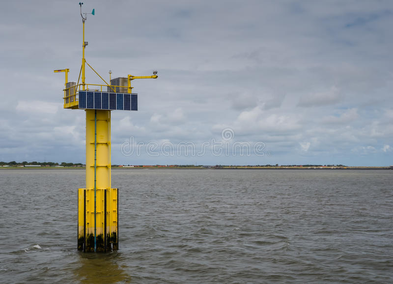 Measuring unit for wave and tidal energy. Sola panels mounted a measuring unit for wave and tidal energy in the Dutch Waddenzee stock photography