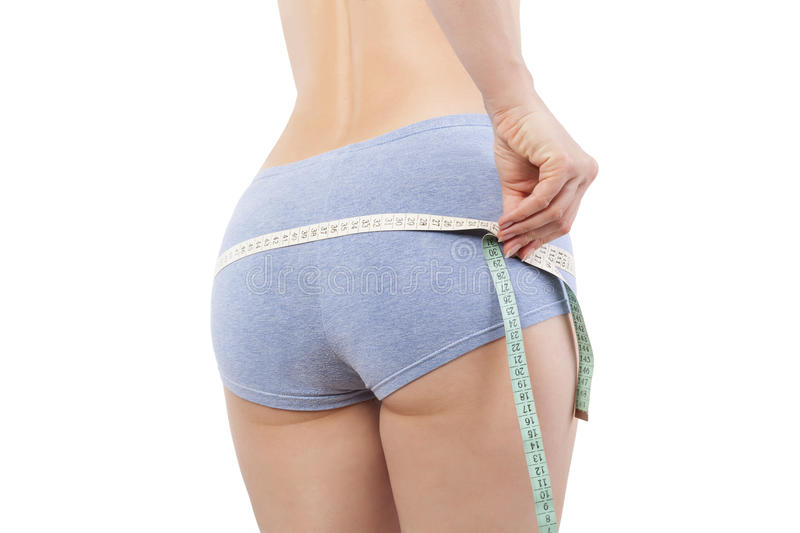 Measuring waistline. Woman in panties measuring her waistline with tape measure isolated on white background. Diet, detox and weight loss concept royalty free stock photography