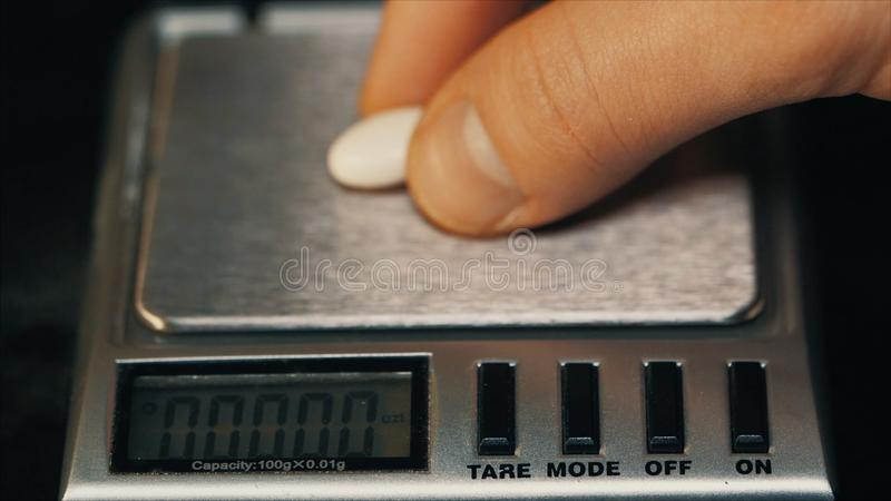 Measuring weight white pills. Weighs the tablet macro. Doctor measures weight pills close-up royalty free stock images
