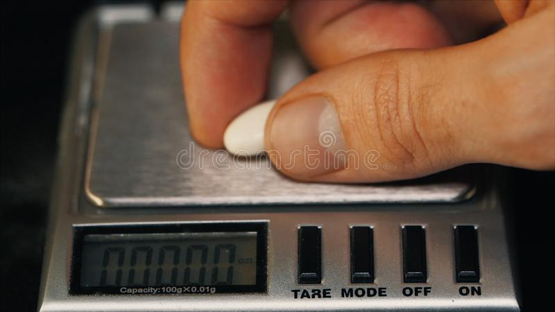Measuring weight white pills. Weighs the tablet macro. Doctor measures weight pills close-up royalty free stock photos
