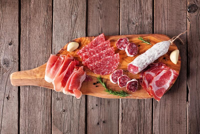 Meat appetizer platter with sausage, prosciutto, ham and salami, top view on a serving board against wood royalty free stock image
