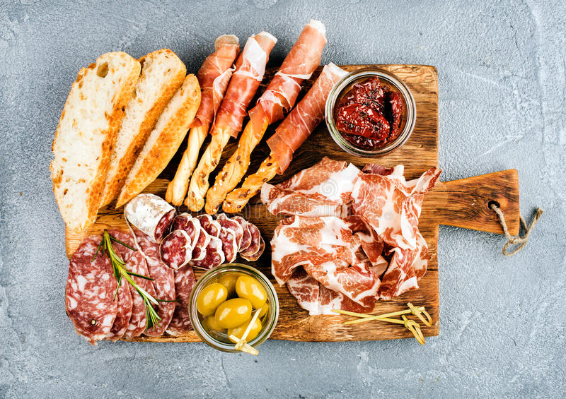 Meat appetizer selection or wine snack set. Variety of smoked meat, salami, prosciutto, bread sticks, baguette, olives. And sun-dried tomatoes on rustic wooden stock photos