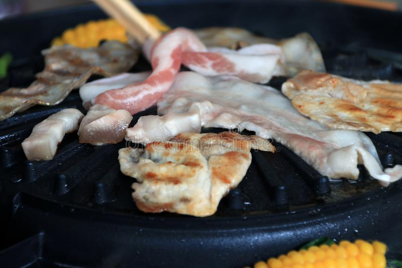 Meat, bacon and streaky pork grilled on the black electric grill with corn boil at the side. Meat, bacon and streaky pork grilled on the black electric grill stock image