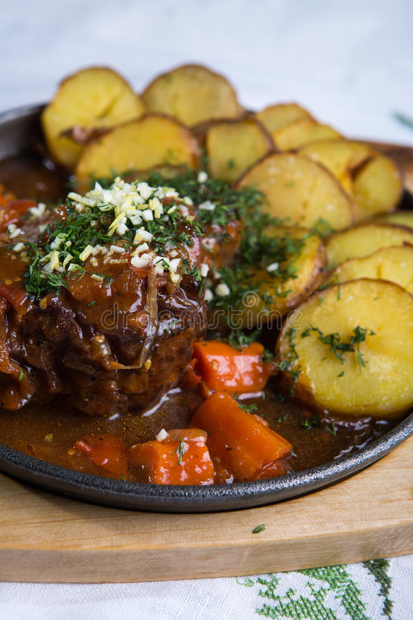 Meat with baked potatoes stock image
