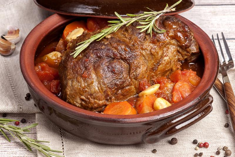 Meat baked with vegetables. A large piece of meat baked with vegetables and herbs on an earthenware plate. Food for ketogenic diet. Cooked in the home kitchen royalty free stock photography