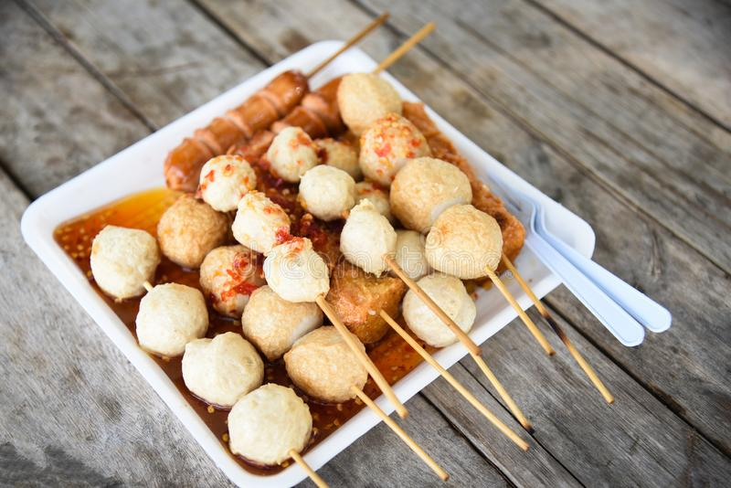 Meat ball , fish ball and sausage hotdog grilled on stick on tray with wooden background Thai style food royalty free stock photography