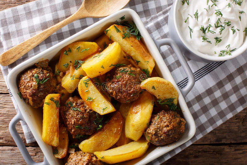 Meat balls with potatoes in a baking dish and sour cream close-up on a table. horizontal top view. Meat balls with potatoes in a baking dish and sour cream close stock photography