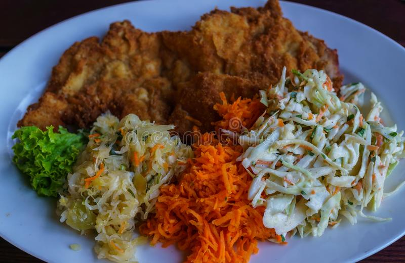 Meat in batter on a plate along with salads from cabbage and carrots and greens stock images