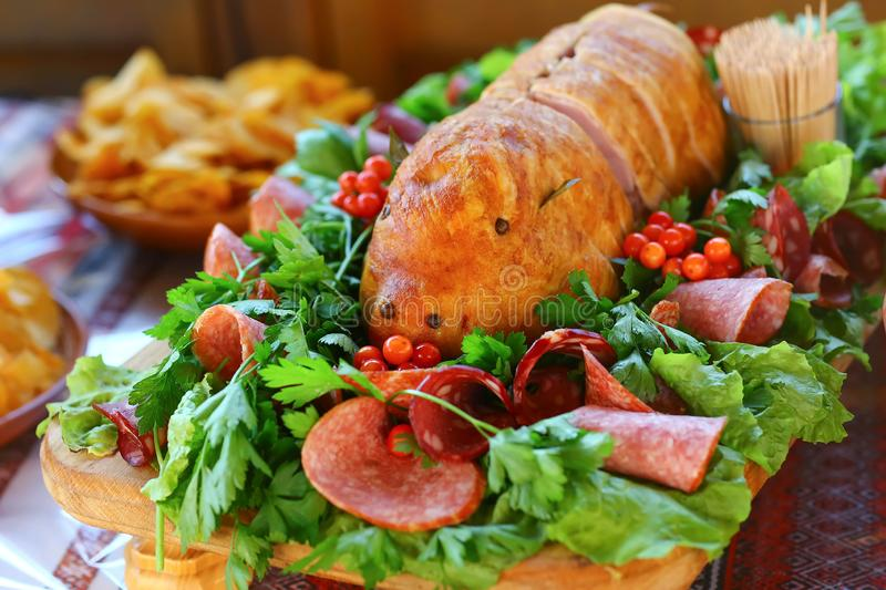 Meat buffet. Catering services background with meat in the form of a pig and vegetables on a Table stock image