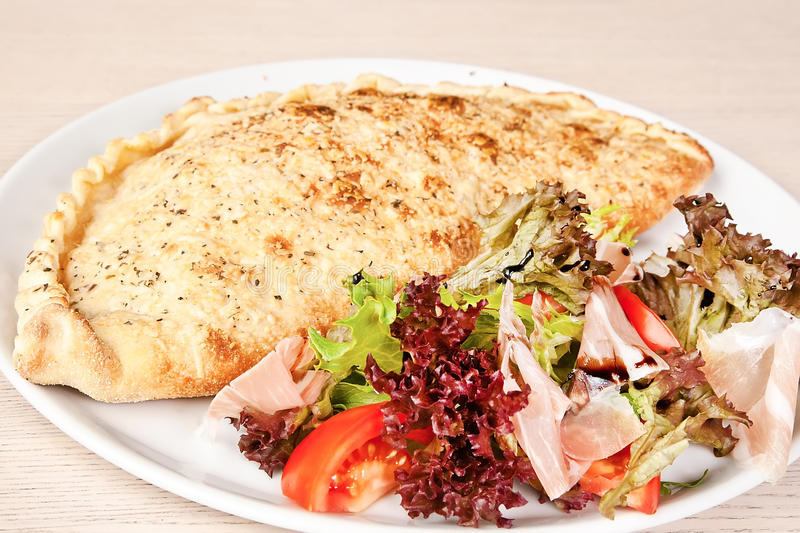 Meat calzone. Calzone with salami, ham, tomatoes and lettuce stock images