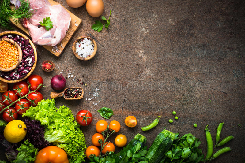 Meat cheese beans and vegetables on dark stone table. stock photos