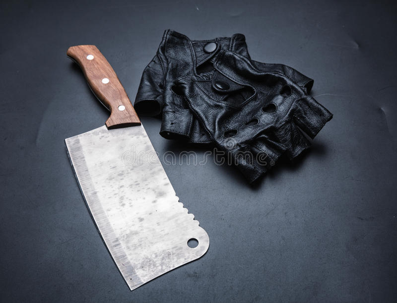 Meat cleaver and fingerless leather gloves. Isolated on black background. Instrument collection of bloody killer maniac stock photo