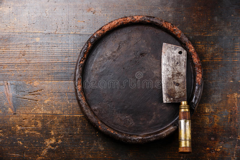 Meat cleaver and stone block. Butcher Meat cleaver and Round stone block on dark wooden background stock photography