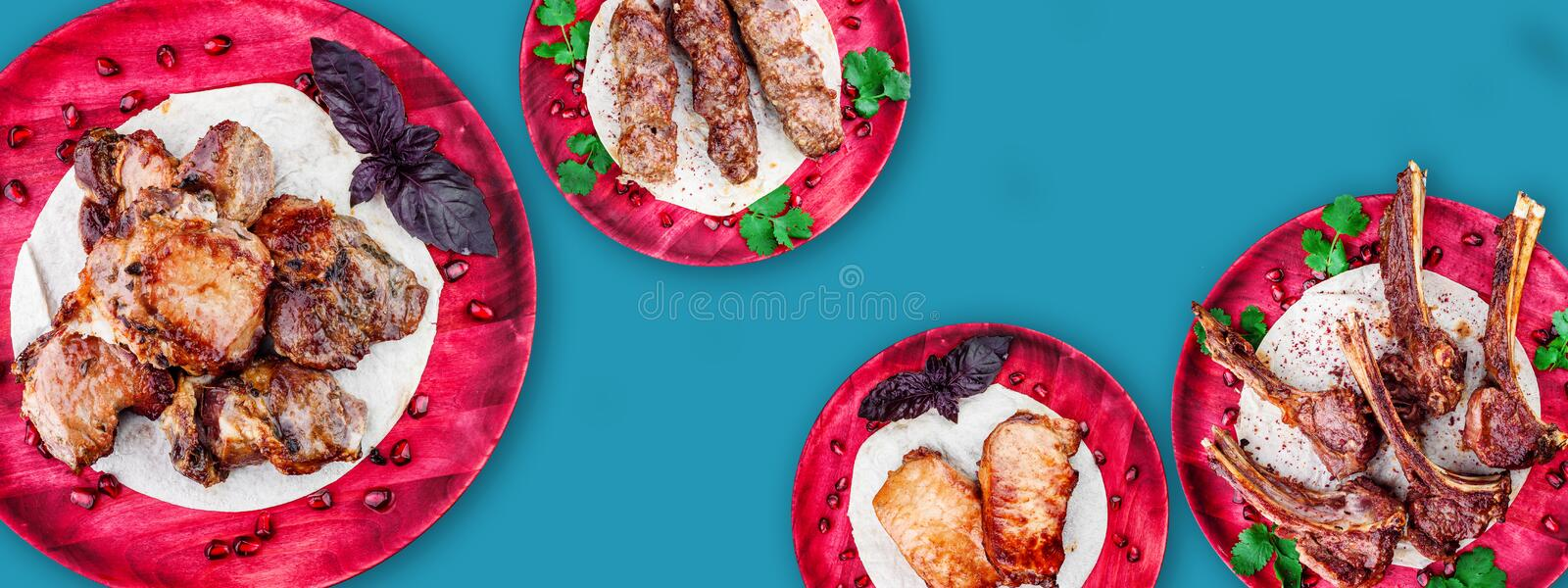 Meat collage. veal ribs, pork, veal and beef barbecue on wooden red plates isolated on a blue background. top view. royalty free stock photography