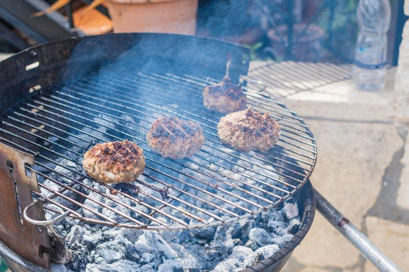 Meat cutlet lies on a heated grill of outdoor cafe or greek tavern. freshly grilled burger meat. royalty free stock photography