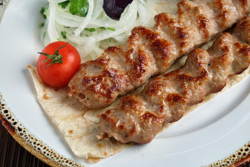 Meat dish lula kebab. Lula kebab meat dish with vegetable side dish in a beautiful serving on a white plate. restaurant menu royalty free stock photo