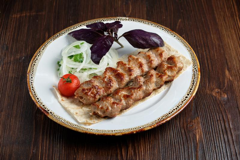 Meat dish lula kebab. Lula kebab meat dish with vegetable side dish in a beautiful serving on a white plate. restaurant menu stock images