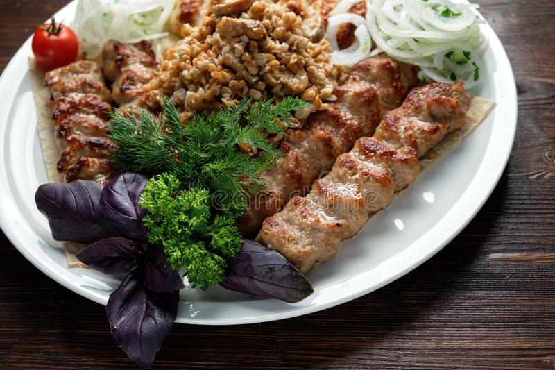 Meat dish lula kebab. Lula kebab meat dish with vegetable side dish in a beautiful serving on a white plate. restaurant menu royalty free stock image