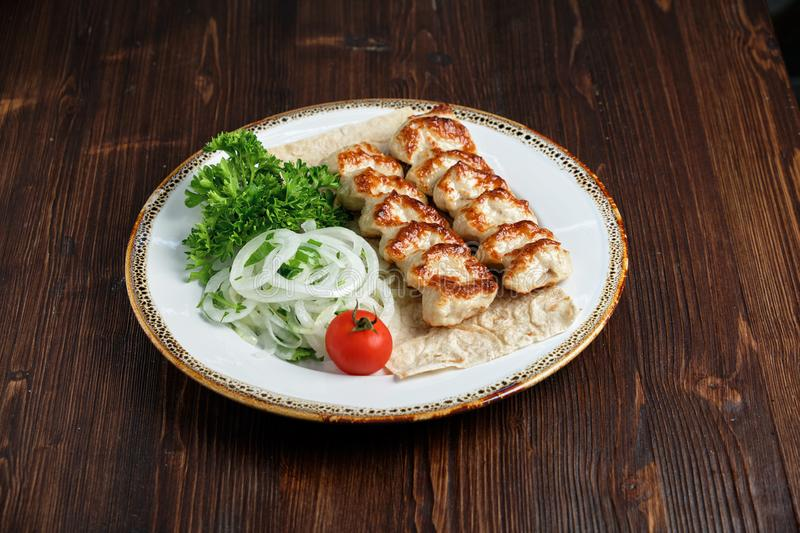 Meat dish lula kebab. Lula kebab meat dish with vegetable side dish in a beautiful serving on a white plate. restaurant menu stock photo