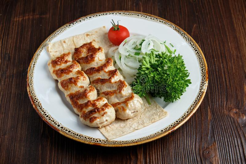 Meat dish lula kebab. Lula kebab meat dish with vegetable side dish in a beautiful serving on a white plate. restaurant menu stock photography