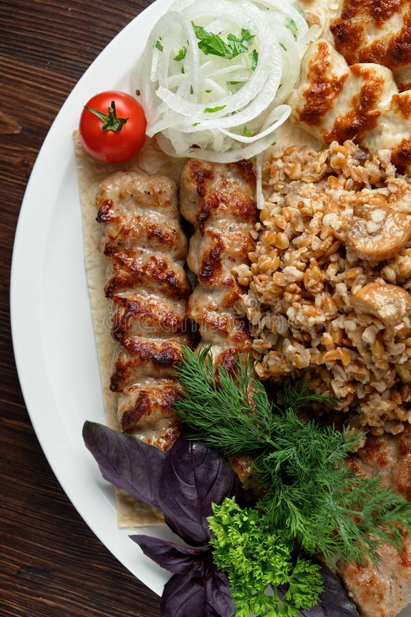 Meat dish lula kebab. Lula kebab meat dish with vegetable side dish in a beautiful serving on a white plate. restaurant menu stock photos