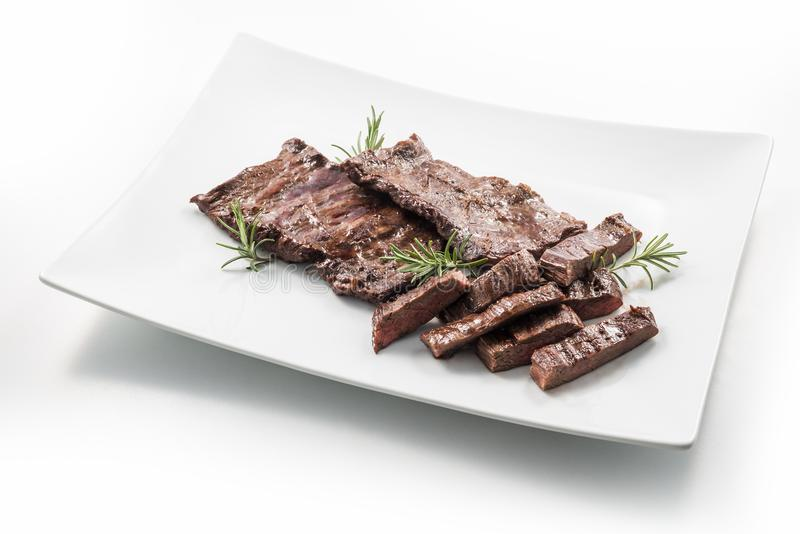 Meat dish Skirt Steak. Square white plate of sliced skirt steak and rosemary royalty free stock photography