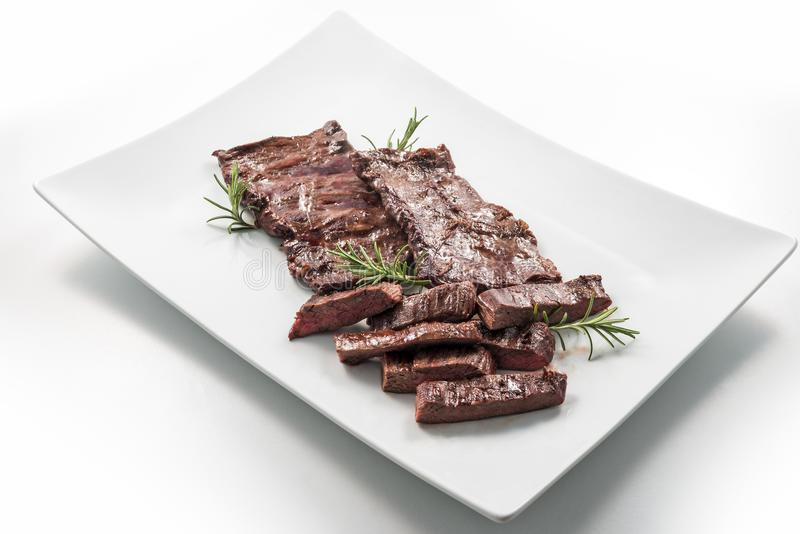 Meat dish Skirt Steak. Square white plate of sliced skirt steak and rosemary royalty free stock photos
