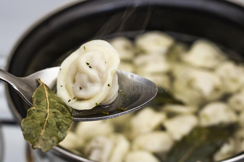 Meat dumplings are boiled in a pot of boiling water royalty free stock image