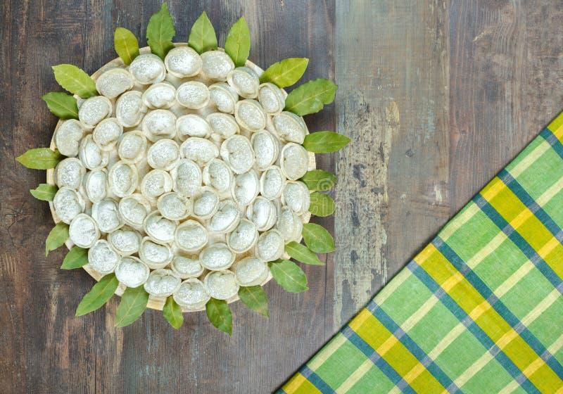 Meat dumplings - russian pelmeni on wooden background royalty free stock image