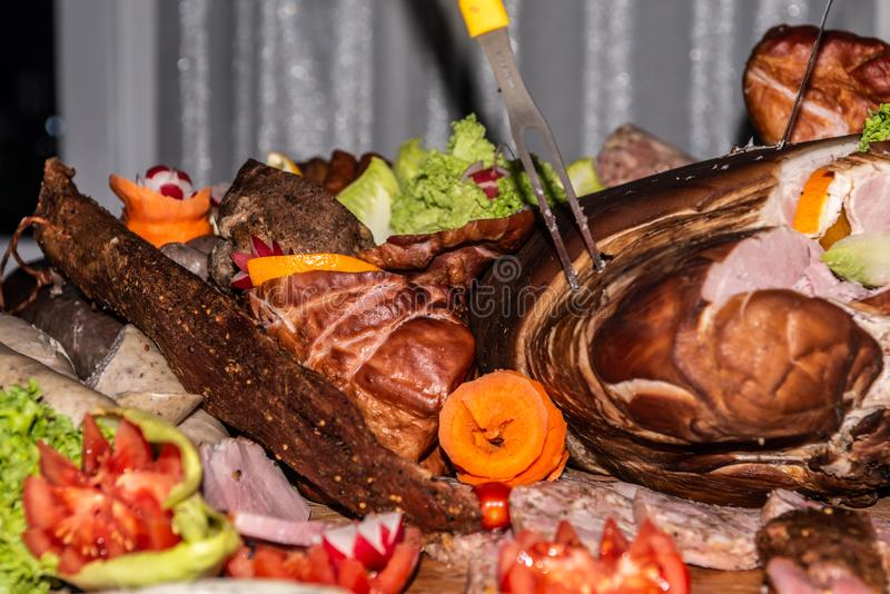 Meat Food tray with pieces of sliced ham, sausage tomatoes and vegetable cutting sausage cured meat on celebratory table stock photography