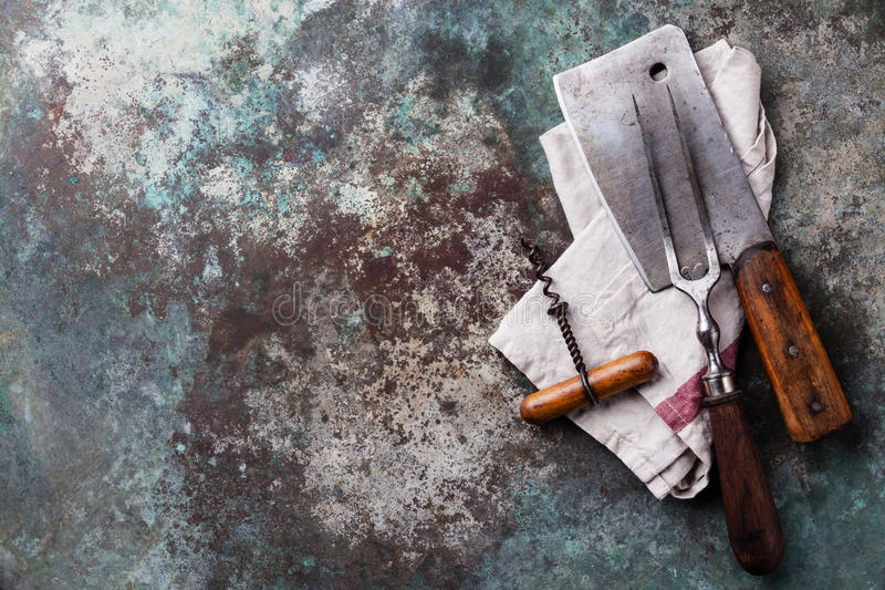 Meat Fork and Cleaver. Vintage meat Fork and Cleaver on metal background stock image