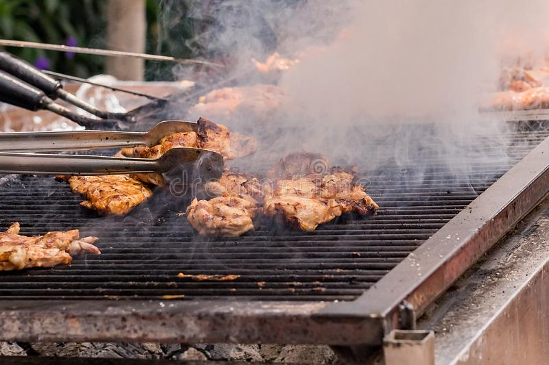 Meat is fried on the grill on the coals. stock photography