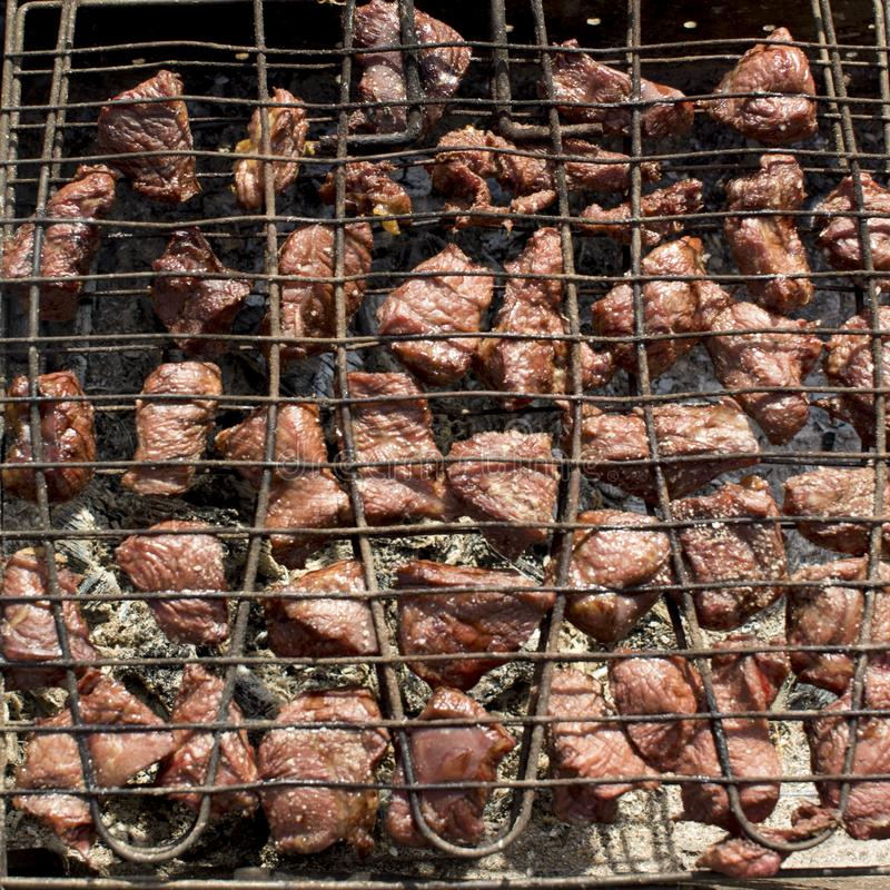 meat is fried on the grill over the coals stock photography