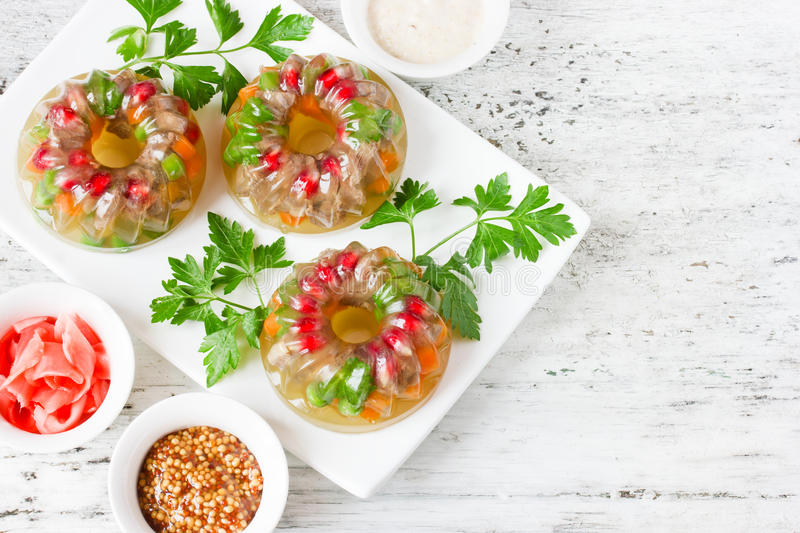 Meat galantine aspic with carrot, pomegranate, peas, parsley on royalty free stock photo