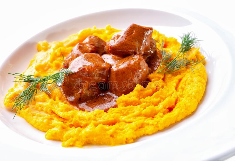 Meat goulash and mashed boiled yellow peas close-up on white plate. Meat goulash and mashed boiled yellow peas decorated with sprigs of fresh dill close-up on royalty free stock photography