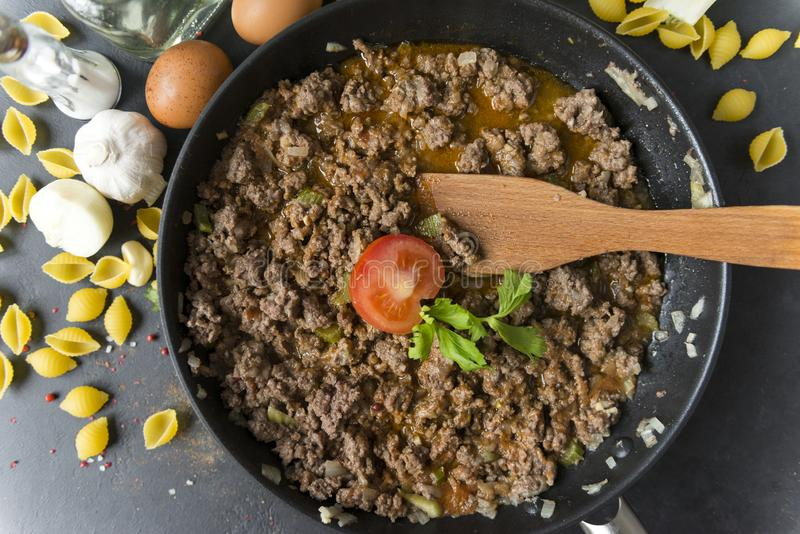 Meat gravy with tomato in a pan , wooden spatula, shell paste, eggs, garlic, onion, spices, butter, top view royalty free stock photos