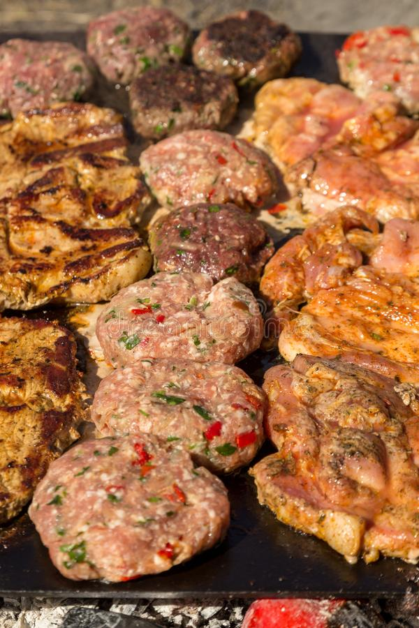 Meat grilled pork with vegetables. Meat balls and steak during grilling. Close up royalty free stock photos