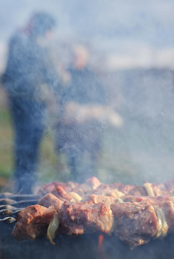 Meat grilling over a barbecue fire. Meat grilling over barbecue fire with smoke rising from sizzling kebabs to cause smoky haze people visible distance cooking stock photos