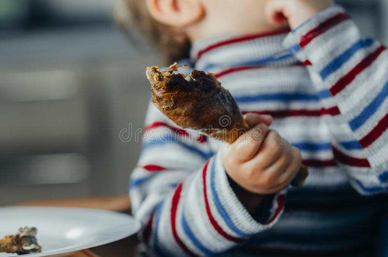 Meat in hand roasted. The child holds the leg, close-up, beautiful, juicy royalty free stock photo