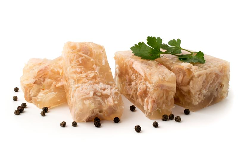 Meat jelly cut in slices with the parsley leaves and black pepper on a white, closeup. stock images