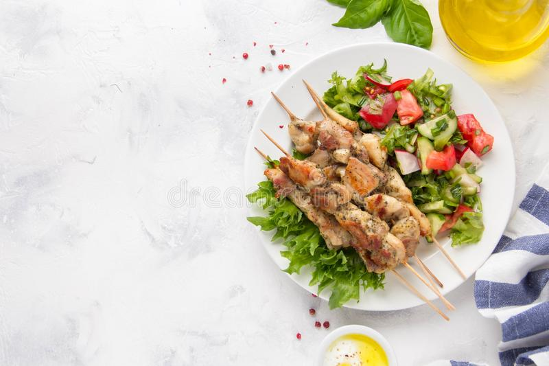 Meat kebabs (chicken, Turkey, pork) on wooden skewers with vegetable salad and yogurt sauce. Spring picnic, grilled food, stock photo