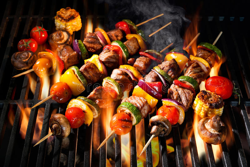Meat kebabs with vegetables on flaming grill stock photos