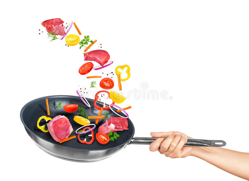 Meat and mix vegetables fall into frying pan stock photo