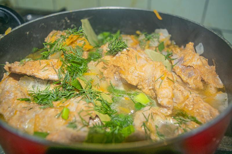 Meat with onions, carrots, dill and Bay leaf is stewed in a saucepan. Home cooking stock images