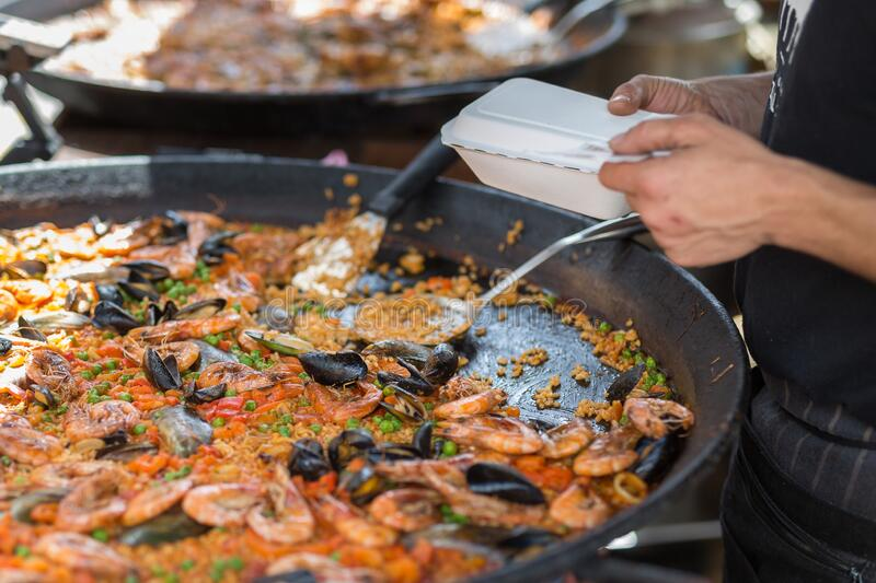 Meat Paella in a Big Black Pan: Rice, Chicken and Beans stock images