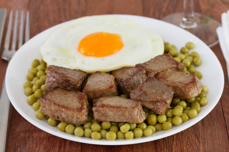 Meat with peas and fried egg stock images