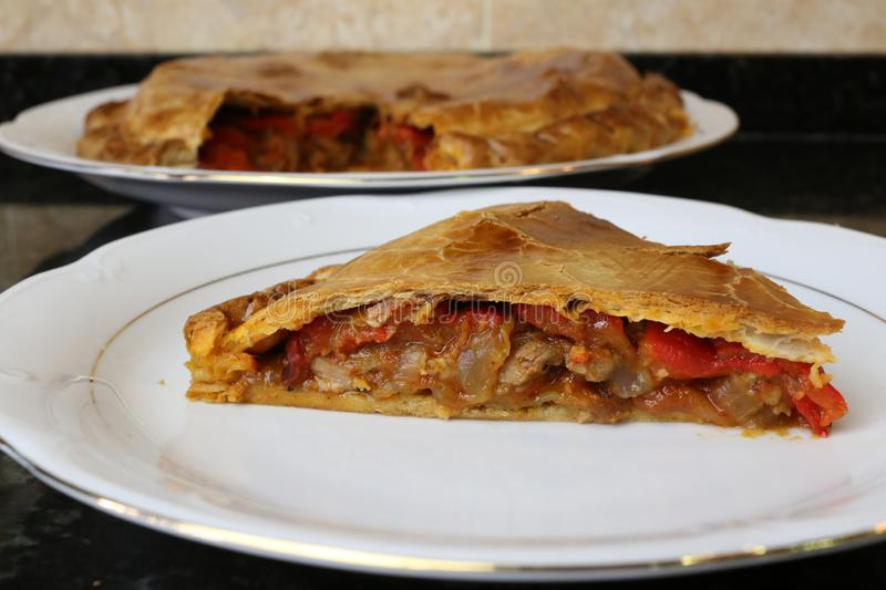 Meat pie traditional home cooking. The meat empanada is a traditional Andalusian and Spanish home cooking meal. The pie is on a white plate on a dark background royalty free stock photos