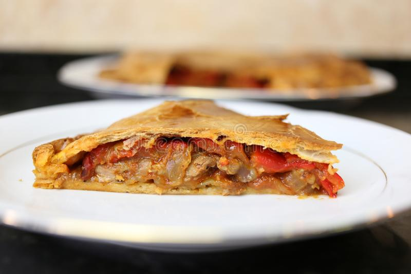 Meat pie traditional home cooking. The meat empanada is a traditional Andalusian and Spanish home cooking meal. The pie is on a white plate on a dark background royalty free stock photo