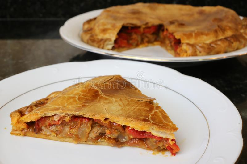 Meat pie traditional home cooking. The meat empanada is a traditional Andalusian and Spanish home cooking meal. The pie is on a white plate on a dark background stock image